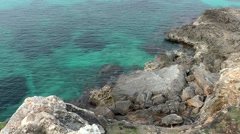 Spain Mallorca Island Cala Blava 010 mottled turquoise water and rocky shore Stock Footage