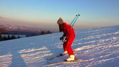 4K Sunset ski. Woman skier go down on ski route down against mountain slopes. Stock Footage