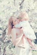 Happy life moments mother hugging child in sunny spring flowering garden Stock Photos
