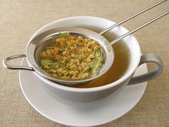 Tilia flowers tea in tea strainer - stock photo