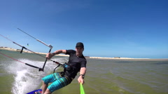Smiling kiteboarder riding in flat lagoon Stock Footage