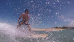 CLOSE UP: Young surfer learning how to surf on small waves - stock footage