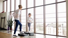 Mother and daughter doing yoga in the gym Stock Footage