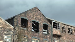 Urban decay derelict factory broken windows stormy sky Stock Footage