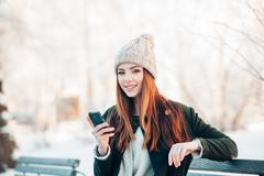 Stock Photo of young woman in winter park talking mobile phone, sms, sitting on the bench