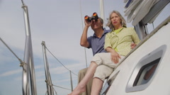 Senior couple looking through binoculars on sailboat together. Shot on RED EPIC - stock footage