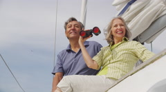 Senior couple looking through binoculars on sailboat together. Shot on RED EPIC Stock Footage