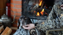 Hunter with dog are sitting by the fireplace. - stock footage