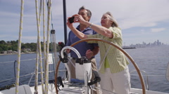 Senior couple behind the wheel of sailboat together. Shot on RED EPIC for high Stock Footage