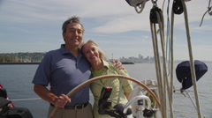 Senior couple behind the wheel of sailboat together. Shot on RED EPIC for high - stock footage