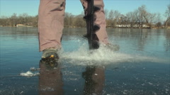 Drilling ice fishing hole in clear frozen lake Stock Footage