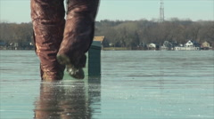 Ice fisher walks toward his tackle box on clear frozen lake Stock Footage