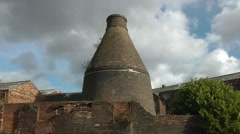 Decaying old conical bottle kiln red brick skyline Stock Footage
