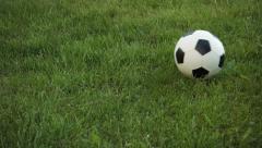 Football Rolling across Frame on Grassy Field - stock footage