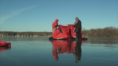 Setting up ice fishing tent on clear frozen lake in windy weather Stock Footage