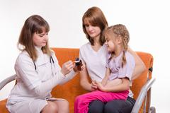 Doctor pediatrician examines a sick child at home in the presence of my mothe - stock photo