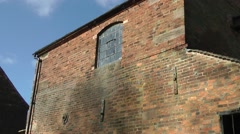 Red brick old factory architecture watermill blue sky moving clouds Stock Footage