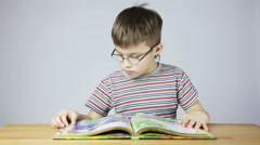 Boy with glasses reading a book Stock Footage