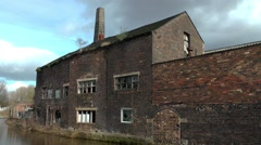 Old decaying factory canal canalside red brick dramatic Stock Footage