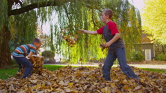 Children playing in fall leaves. Shot on RED EPIC for high quality 4K, UHD, - stock footage