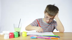 Preschool boy draws a picture of a pencil - stock footage