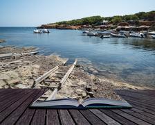 Landscape image of old Mediteranean fishing village conceptual book image - stock photo