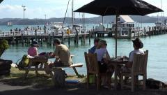 People eat at beach front cafe, Russell, Bay of Islands, New Zealand Stock Footage