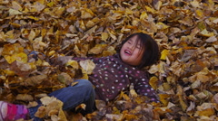 Young girl playing in fall leaves. Shot on RED EPIC for high quality 4K, UHD, - stock footage