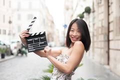 Young asian woman smiling and shows clapperboard urban scene - stock photo