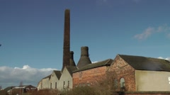 Pottery factory old bottle kilns chimney blue sky Stock Footage