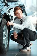 Handsome young man in dealership - stock photo