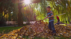 Young boys raking fall leaves. Shot on RED EPIC for high quality 4K, UHD, Ultra Stock Footage