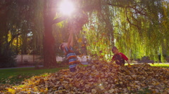 Children playing in fall leaves. Shot on RED EPIC for high quality 4K, UHD, Stock Footage