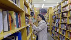 Mixed Race Teen Browses Book Store Or Library, Drinks Coffee Stock Footage