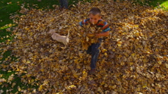 Overhead shot of children playing in fall leaves. Shot on RED EPIC for high - stock footage