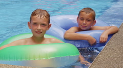 Two boys in pool with inner tubes Stock Footage