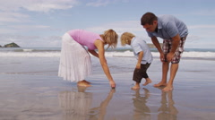 Parents and young son looking for shells at beach, Costa Rica - stock footage