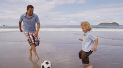 Father and son kicking soccer ball together at beach Stock Footage