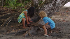 Two young kids play on homemade teeter totter at beach, Costa Rica Stock Footage