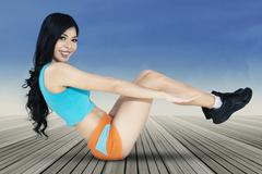 Long hair woman doing sit-up exercise - stock photo
