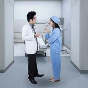 Male doctor talking with a female surgeon - stock photo