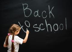 little girl wrote in chalk on black chalkboard - stock photo