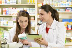 Two young female pharmacist in a drugstore working on a tablet pc - stock photo