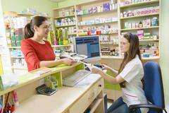 Young female pharmacist having a customer in a drugstore holding a receipt - stock photo