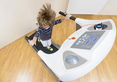 Cute boy running treadmill at home Stock Photos