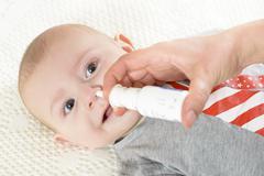 Woman using nasal spray for baby Stock Photos