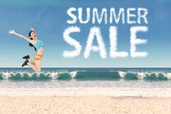 Woman with summer sale clouds at beach Stock Photos