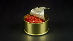 Red caviar in a tin can rotation on the black background, 4K Stock Footage