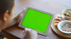 Man using digital tablet with a green screen to add your own custom content - stock footage