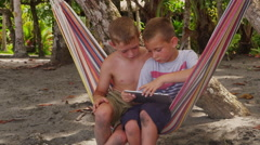 Two young boys using digital tablet in hammock at beach Stock Footage